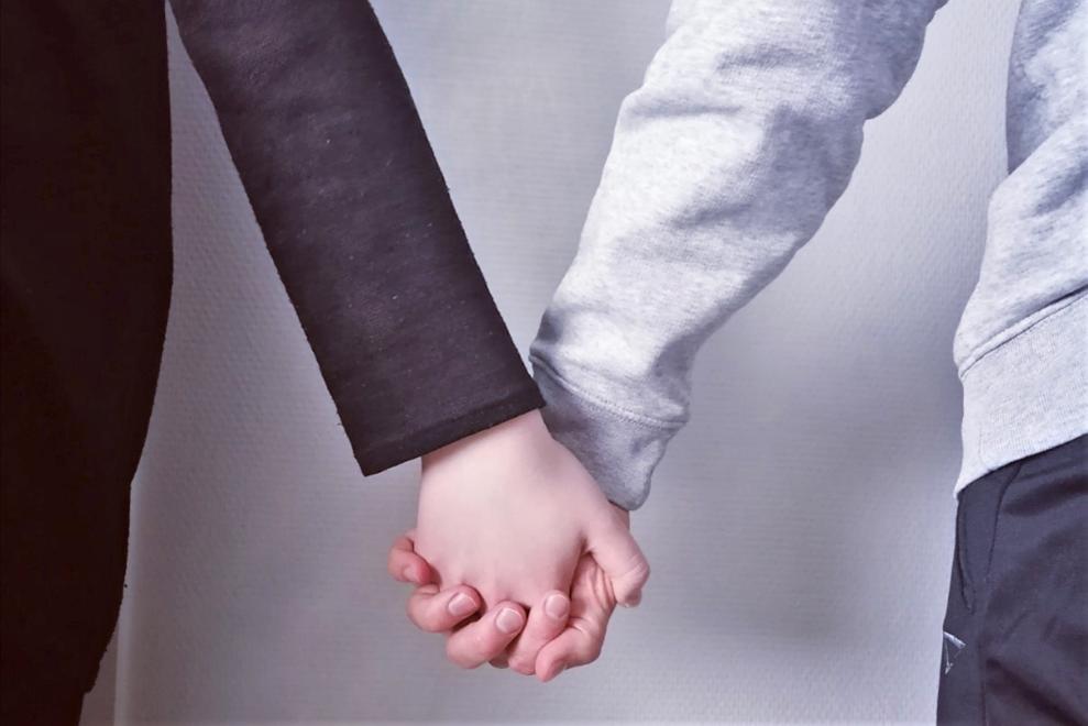 Valokuva, jossa kaksi ihmistä käsikädessä.