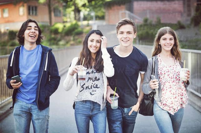 Valokuva, jossa kaksi tyttöä ja kaksi poikaa kävelee sillalla ja katsoo hymyillen kameraan.