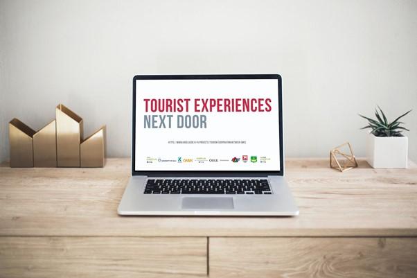 Valokuva pöydällä olevasta kannettavasta tietokoneesta, jonka näytölle on teksti Tourist Experiences Next Door.