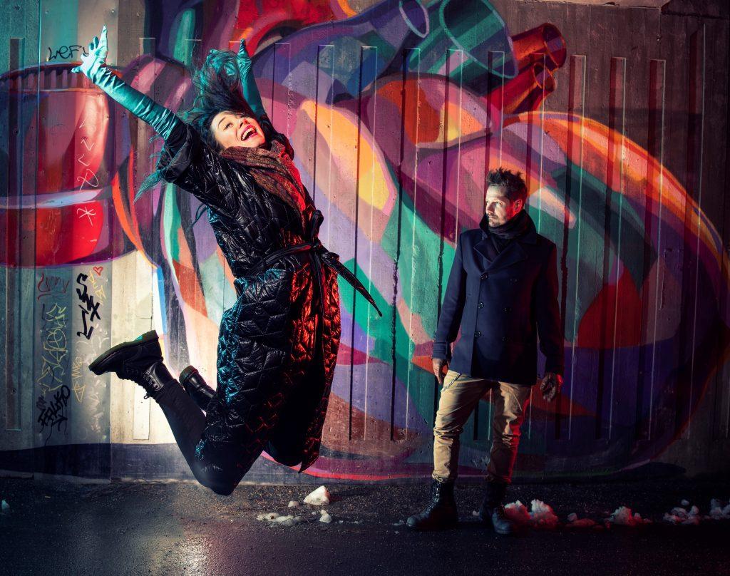 Valokuva, jossa nainen ja mies, taustalla graffitiseinä.