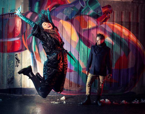 Valokuvassa nainen ja mies, taustalla graffitiseinä.
