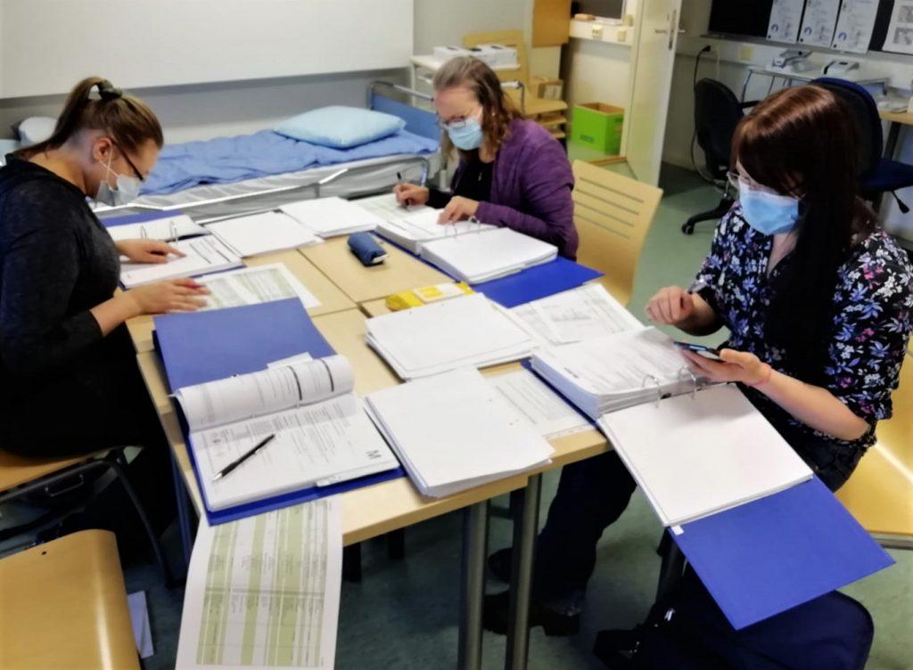 Valokuva, jossa kolme ihmistä istuu pöydän ääressä ja tutkii kansioista papereita.
