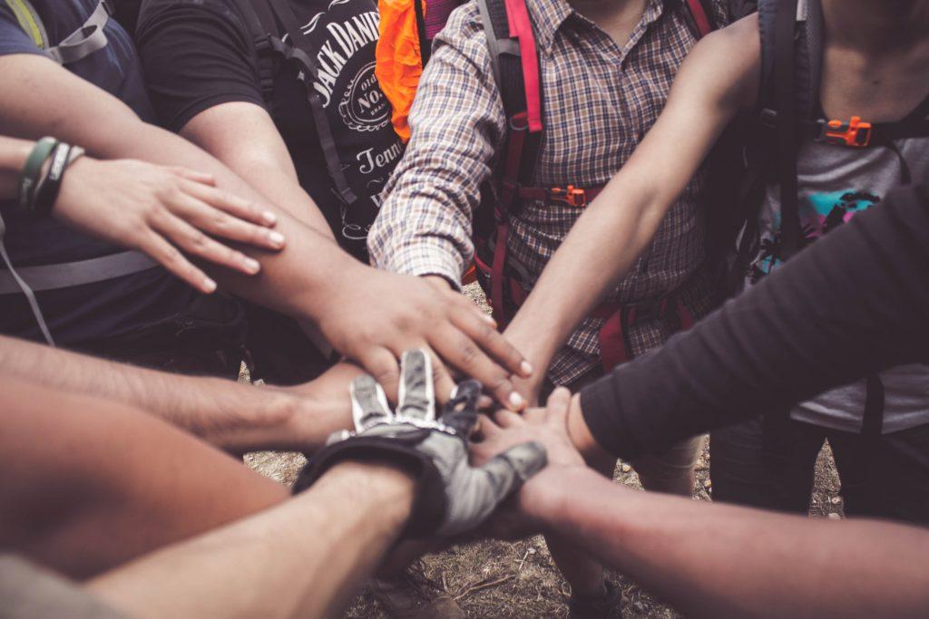 Valokuvassa nuoria kädet ympyrässä.