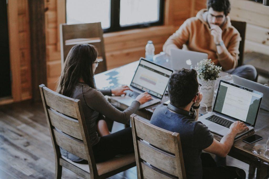 Kolme ihmistä istuu pöydän ääressä tietokoneiden kanssa.