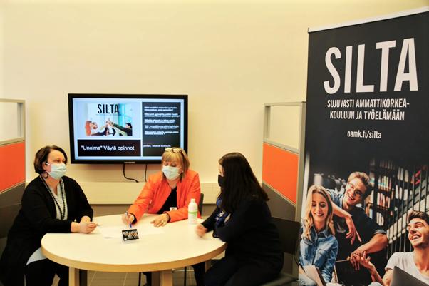 Valokuva, jossa kolme ihmistä istuu pöydän ääressä.