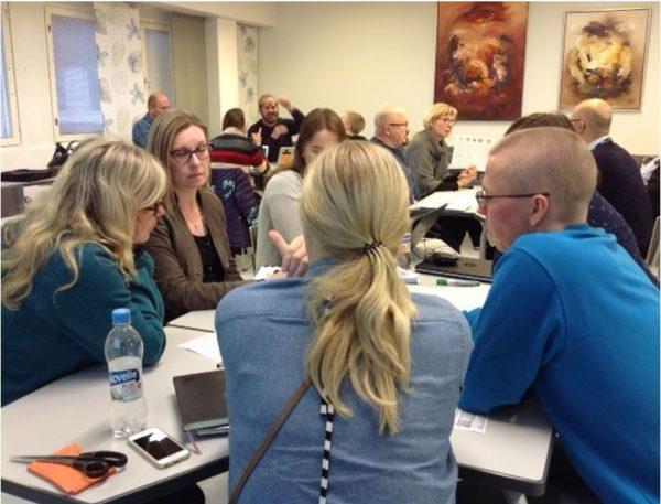 Valokuva, jossa ihmisiä luokkatilassa tekemässä ryhmätyötä.