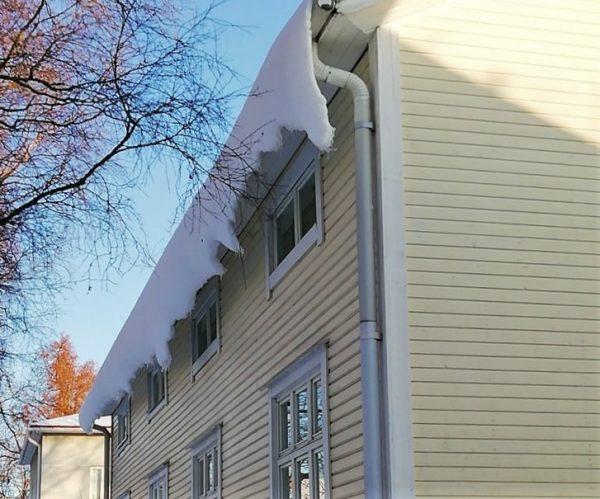 Valokuvassa talo, jonka katolta roikkuu lunta.