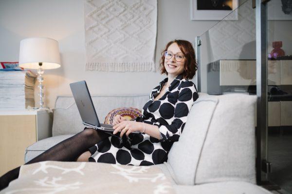 Valokuvassa nainen istuu sohvalla tietokone sylissä.