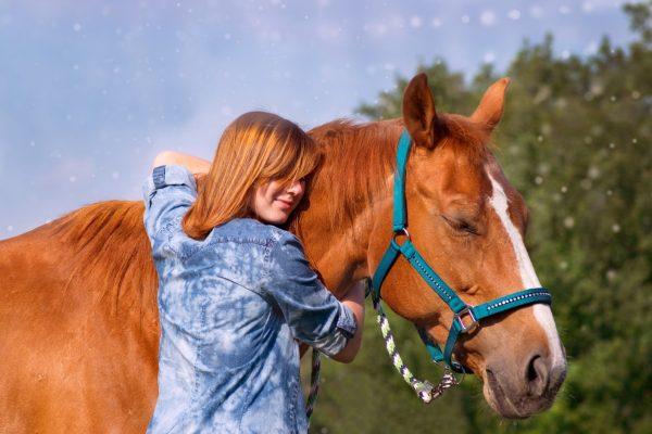 Valokuva, jossa nainen halaa hevosta.