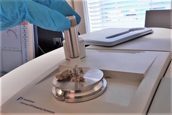 Valokuvassa FTIR-spektrometri, johon ollaan asettamassa maanäytettä.