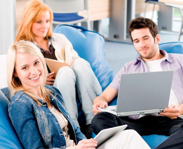 Valokuvassa kolme ihmistä istuu säkkituoleilla ja katsoo kannettavaa tietokonetta.
