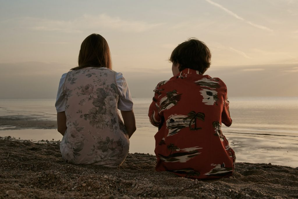 Valokuva, jossa kaksi teini-ikäistä istuu rannalla selkä kameraanpäin.