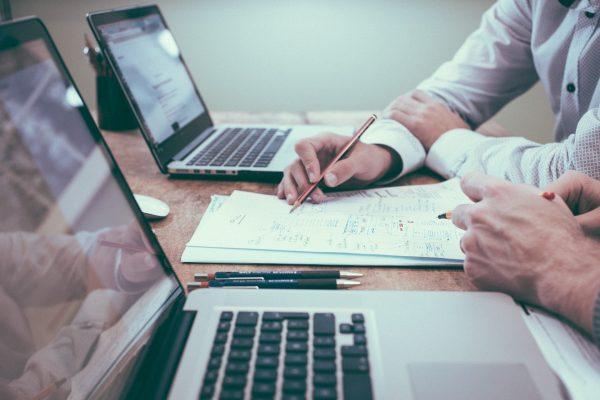 Valokuvassa kaksi kannettavaa tietokonetta ja papereita niiden välissä.