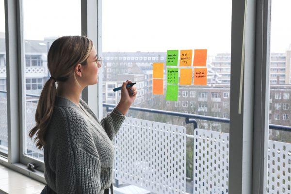 Valokuva naisesta kirjoittamassa post-it-lapuille, jotka on kiinnitetty ikkunaan.