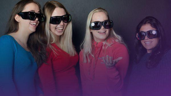 Valokuva, jossa neljä yläkoululaista virtuaalilasit päässä.