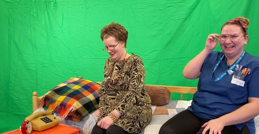 Valokuvassa Johanna Rantala ja Minna Rantala istuvat puusängyllä ja nauravat.