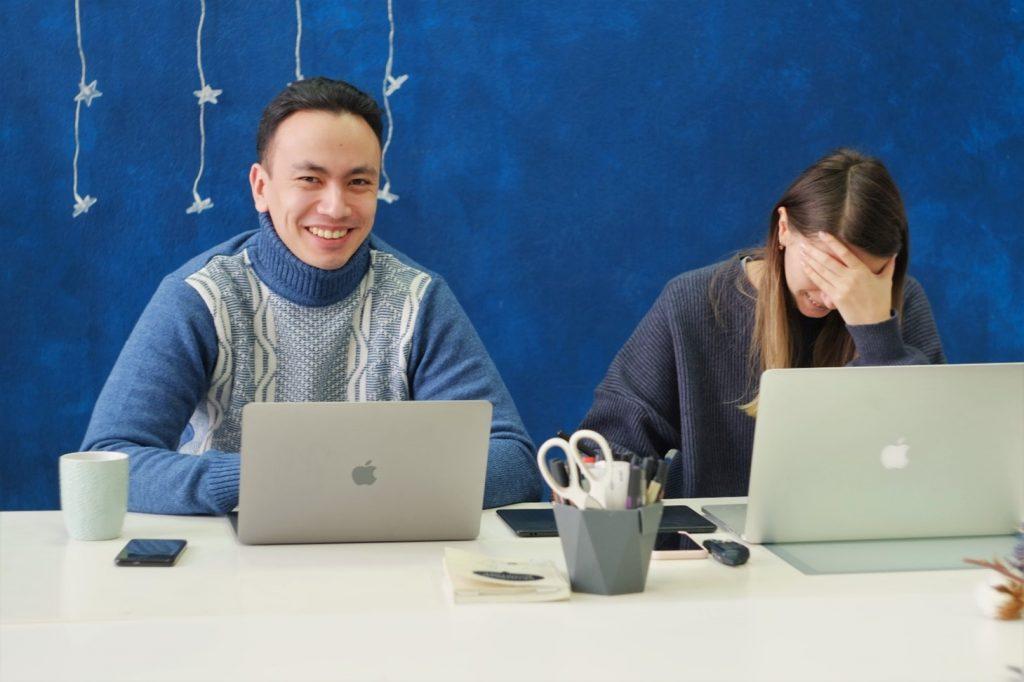 Valokuva, jossa mies ja nainen istuu pöydän takana läppäreiden kanssa ja nauravat.