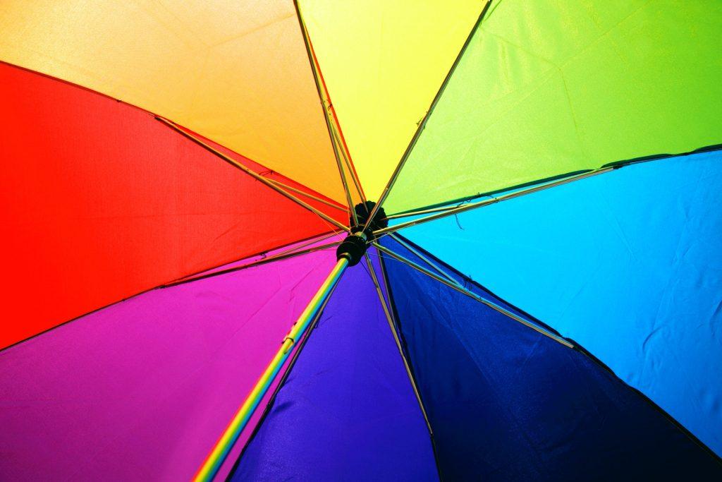 Valokuvassa sateenkaaren väreissä oleva sateenvarjo.